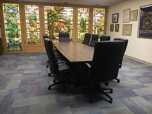 Board Room meeting table with chairs and O.C. Barber Mansion stained-class windows in the background.
